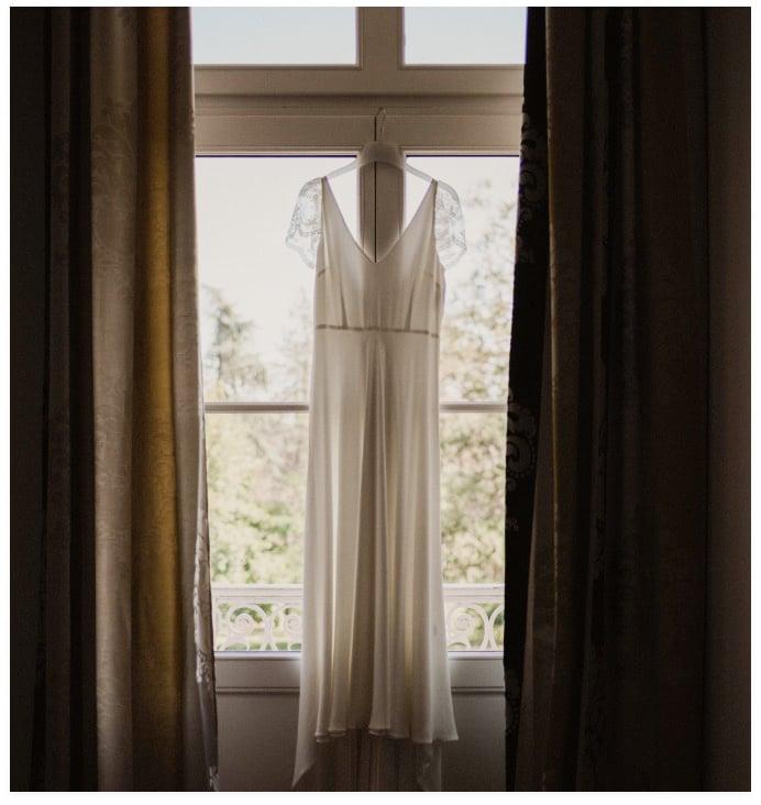 photo avec vue sur la fenêtre depuis la chambre des mariés, avec la robe de mariée blanche accrochée au centre de la fenêtre