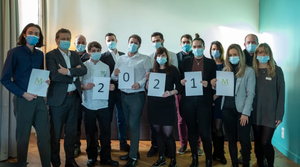 """photo de groupe du Domaine de Montjoie. Le personnel est debout face à l'objectif, certains membres portent des feuilles de papiers portant l'inscription """"2021"""", avec le logo du Domaine de Montjoie"""